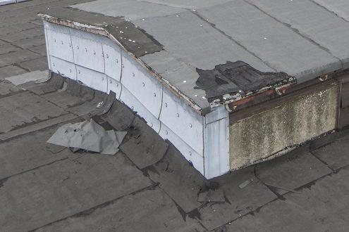Nahaufnahme von Sturmschaden an Dach einer Fabrik