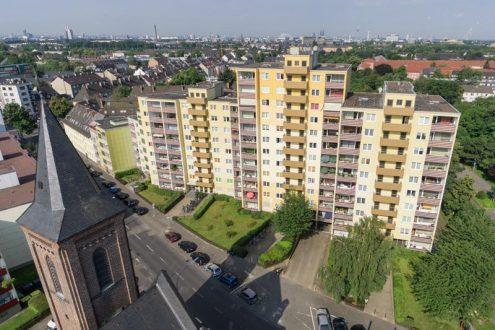 Luftbild von Mietwohnungen und Kirche