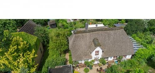 Luftbild einer Immobilie auf dem Land, Schöne Villa mit Reetdach