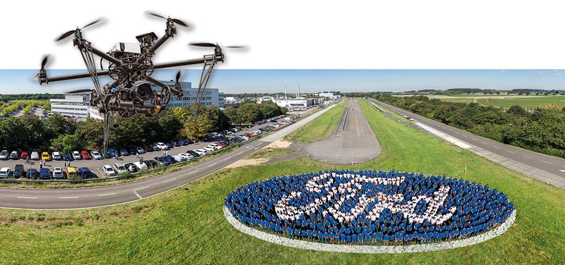 700 Mitarbeiter von Ford in Köln stellen sich bei einer Veranstaltung als Logo für ein Luftbild auf